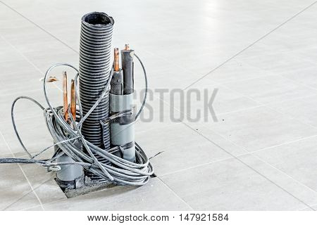 Bunch of various electric cables in corrugated pipe is coming out from the tiled floor ready to be connected into power unit.