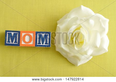 Mom spelled with alphabet blocks and a white artificial rose on a yellow background