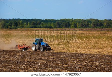 Big blue tractor plows the field and removes the remains of previously mown sunflower. Work agricultural machines. Harvest