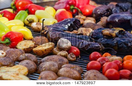 Red yellow green bell peppers potatoes mushrooms tomatoes and eggplant grilled until golden brown. The concept of proper nutrition and a healthy lifestyle. Cooking vegetables on the barbecue.
