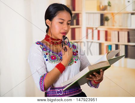 Beautiful young lawyer wearing traditional andean blouse, holding glasses and book reading, bookshelves background.
