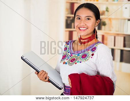 Beautiful young lawyer wearing traditional andean blouse with necklace, holding laptop and red jacket smiling, bookshelves background.