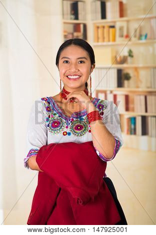 Beautiful young lawyer wearing traditional andean blouse and necklace, holding red jacket while smiling happily, bookshelves background.