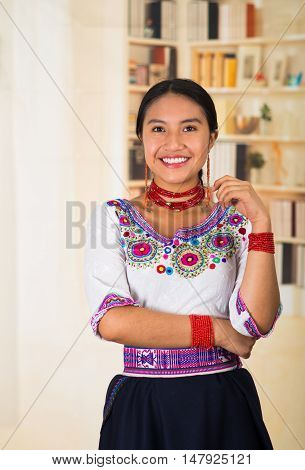 Beautiful young lawyer wearing black skirt, traditional andean blouse with necklace, standing posing for camera, smiling happily, bookshelves background.
