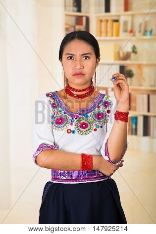 Beautiful young lawyer wearing black skirt, traditional andean blouse with necklace, standing posing for camera, serious facial expression, bookshelves background.