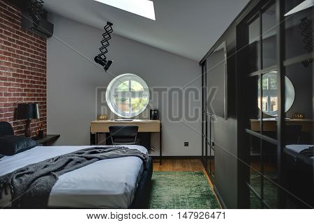 Amazing modern bedroom with brick wall and parquet with green carpet. There is bed, rack with lamp, round window, table with chair, wall with TV and wardrobes. At the top there are lamps and window.