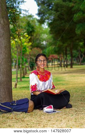 Young woman wearing traditional glasses, andean skirt and blouse with matching red necklace, sitting on grass next to tree in park area, relaxing while reading book, smiling happily.