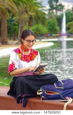 Young woman wearing traditional andean skirt and blouse with matching red necklace, sitting on bench next to lake in park area, relaxing while using tablet, smiling happily.