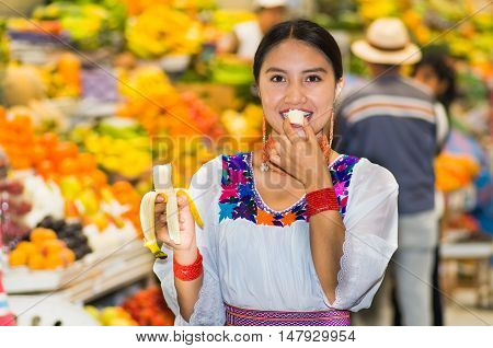 Beautiful young hispanic woman wearing andean traditional blouse posing for camera while eating banana inside fruit market, colorful healthy food selection in background.