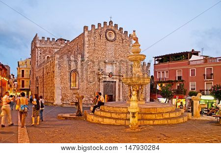 TAORMINA ITALY - OCTOBER 1 2012: The crowded Duomo Square becomes peaceful in the evening its Baroque fountain is the nice place to relax and enjoy the view on St Nicholas Cathedral on October 1 in Taormina.