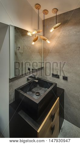 Fancy bathroom with gray textured tiles and glowing lamps. There is sink with tap and mirror. Under the sink there is locker. Vertical.