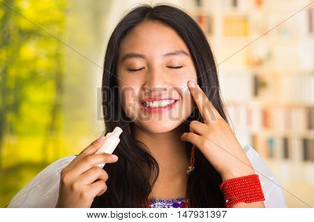 Beautiful hispanic woman wearing white blouse with colorful embroidery, applying cream onto face using finger during makeup routine, smiling happily, garden background.