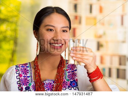 Beautiful hispanic woman wearing white blouse with colorful embroidery, holding three small tubes of cream during makeup routine, garden background.