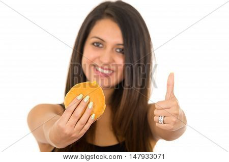 Beautiful young woman posing eating hamburger while giving thumb up to camera, smiling happily, white studio background.