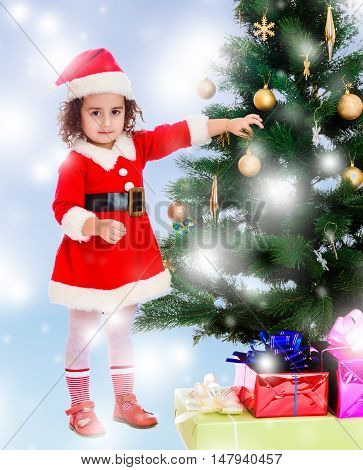 Adorable little curly-haired girl, dressed as Santa Claus decorates a Christmas tree toys.Blue winter background with white snowflakes.