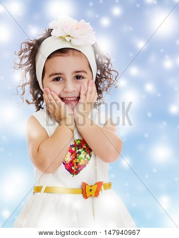 Beautiful little curly girl in a white dress happily surprised. Girl holding hands near the face. Close-up.Blue winter background with white snowflakes.