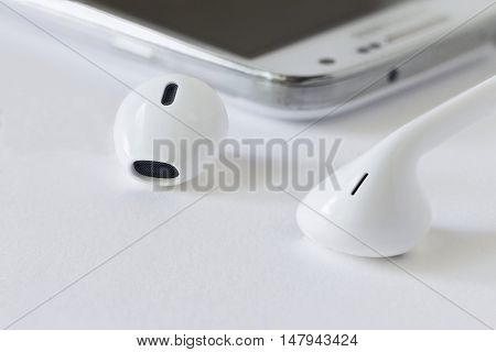 horizontal close up image of the heads of white ear buds connected to a cell phone on white background.