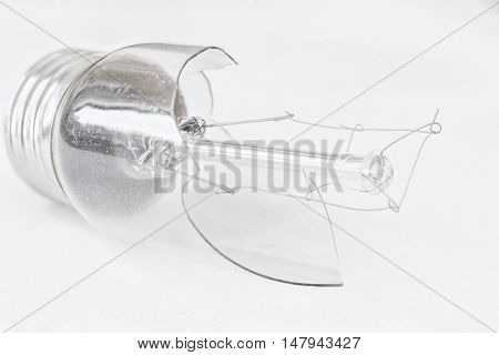 horizontal image of a small broken light bulb isolated on white background.