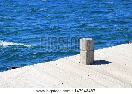 Wooden Boat Mooring Bollard On Jetty By Blue Ocean