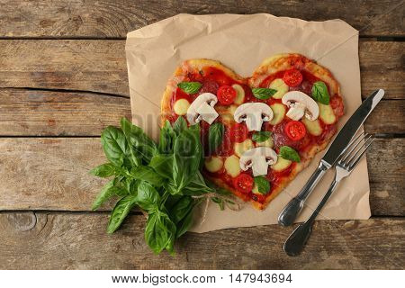 Tasty pizza in heart shape with fresh basil leaves on table