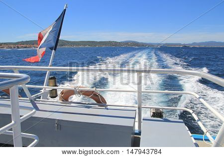 French Tricolour Flag Flying On The Back Of A Boat Leaving A Wake Through The Blue Mediterranean Sea