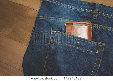 brown leather wallet in jeans back pocket blue