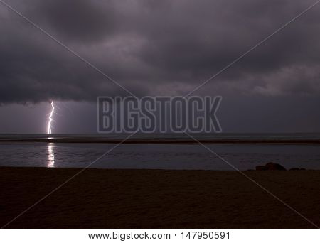 Incredibly sharp lightning with branches hitting the ocean with reflected light