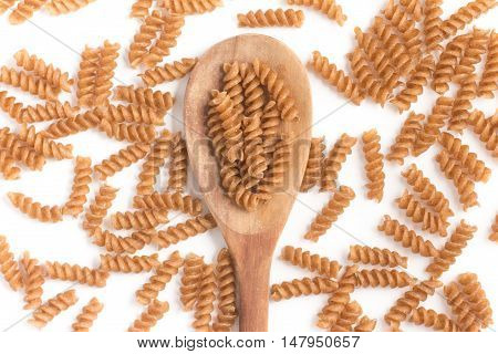 Wholemeal Fusilli into a spoon. Integral Pasta isolated in white background