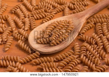 Wholemeal Fusilli into a spoon. Integral Pasta over a wooden table