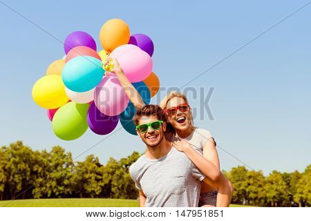 Portrait Of Happy Man With Balloons Piggybacking His Girlfriend