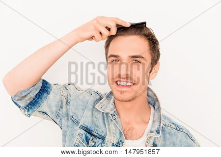 Portrait Of Smiling  Man In Jeans Jacket Combing His Hair
