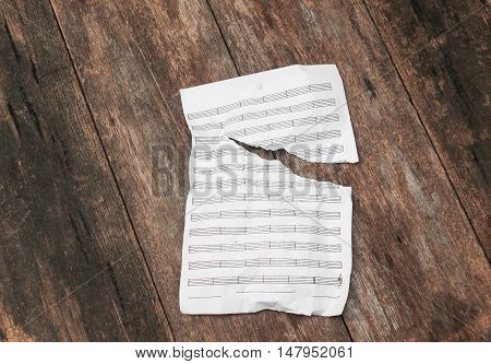 White blank sheet music torn and crumpled on a wooden floor background
