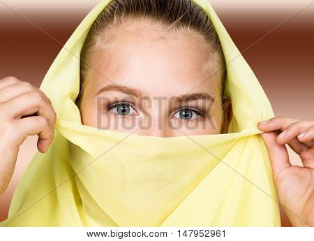 close-up beautiful mysterious eyes eastern woman wearing a yellow hijab.