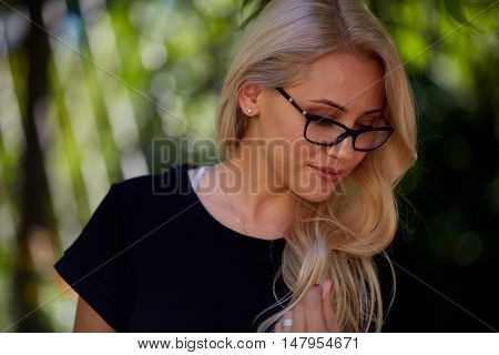 blonde women at black dress and glasses sitting on the bench at park