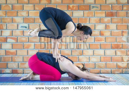 Asians two strong woman practicing advanced yoga against a brown texturized wall