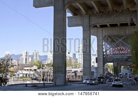 Vancouver, BC - April 20, 2015 - Photo of the entrance to Granville Island, which is a peninsula beneath the south end of Granville Street Bridge. It was a beautiful sunny day with blue skies and the features the city of Vancouver with it's highrises and