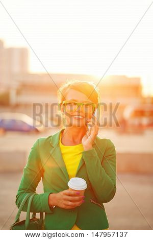 Young attractive woman talking on smartphone. Businesswoman holding a cup of coffee and fashionable bag. A successful and positive. Soft focus. Photographed with backlighting.