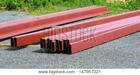 reddish structural steel beams lined up to be being used in construction, Songkhla, Thailand