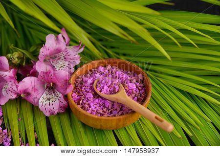 Orchid flowers , bowl ,spoon and palm leaves, closeup