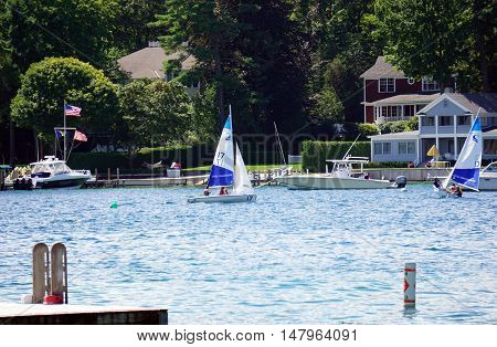 HARBOR POINT, MICHIGAN / UNITED STATES - AUGUST 1, 2016: People enjoy a sailing lesson, provided by Little Traverse Sailors, off the shore of Harbor Point.