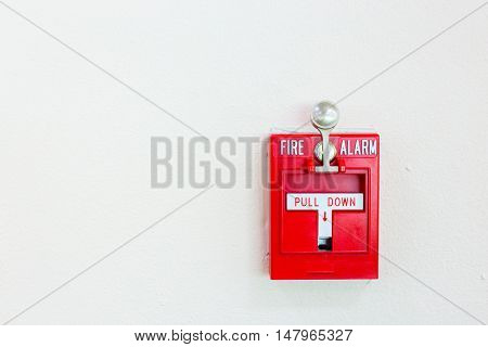 Red fire alarm switch with pull down lever mounted on white wall