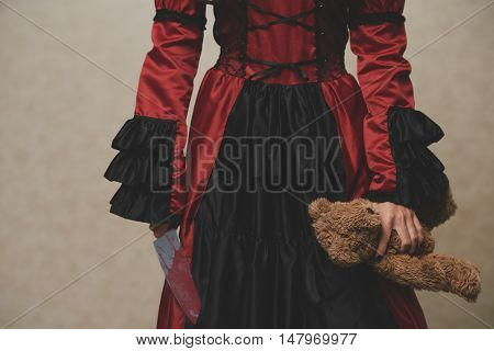 Cropped image of spooky girl carrying teddy bear and sharp knife