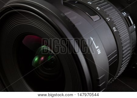 Black camera lens isolated on black background partial view