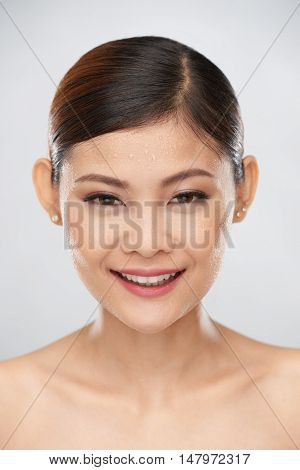 Beautiful smiling woman with drops of water on her face