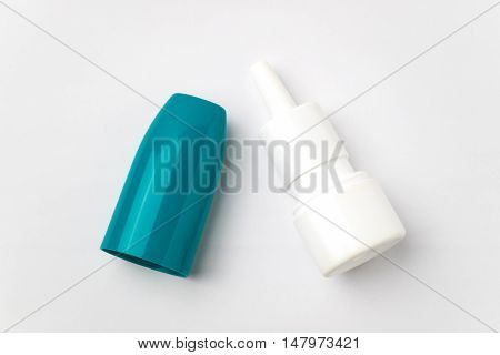 Plastic nasal spray container on white background. Steroid nose sprey bottle with green cap.