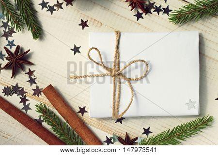 Handmade simple winter craft. Congratulation empty card decorated twine, pine twigs, anise, confetti stars.