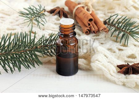 Essential pine or cinnamon oil. Winter fragrances. Glass dropper bottle of aroma oil, pine twigs, cinnamon, knitted plaid.