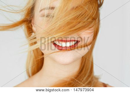 Perfect white smile of red-haired girl, close-up. Widely smiling happy woman portrait. Good dentist, teeth care, whitening concept