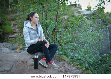 woman hiker sitting on a big stone on top of the mountain with thermos and cup of tea near her.