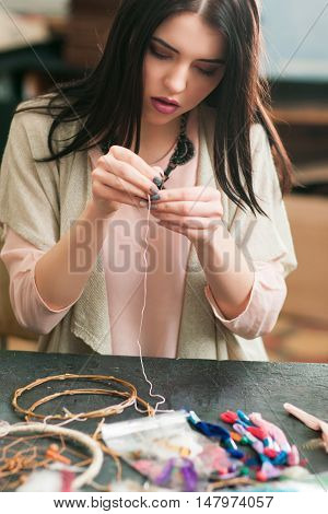 New dream catcher creation in art studio. Female artisan making decoration accessory for bedroom. Workshop, hobby, handicraft, creativity concept